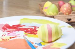 Painting Easter Eggs. A homely Easter egg-painting scene on a wooden table.  Finished eggs in a carton, egg-in-progress, paints,  and paintbrush on a china plate Stock Photos