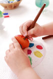 Painting Easter eggs. Cute little girl painting Easter eggs Royalty Free Stock Photo