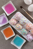Painting Easter eggs. Colored water and brush Stock Image