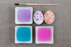 Decoration Easter eggs. Painting Easter eggs, colored water and paintbrush Stock Photo