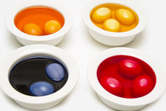 Painting easter eggs in four bowls Royalty Free Stock Photos
