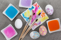 Decoration Easter eggs. Painting Easter eggs, paintbrushes and colored water Royalty Free Stock Photos