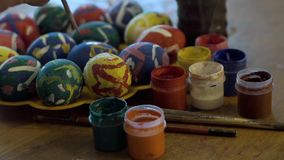 Painting Easter eggs. With paints and a brush