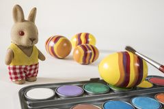 Painting Easter eggs with red brush. Easter bunny and yellow eggs. stock photography