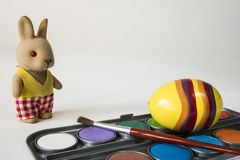 Painting Easter eggs with red brush. Yellow Easter egg and stuffed animal on white background. Space for text royalty free stock photography