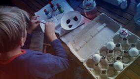 Painting Easter Eggs. Painting white candy coated chocolate Easter eggs with food colouring Royalty Free Stock Photography