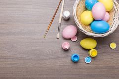 Painting Easter eggs with brushes and paint on wooden background stock photos