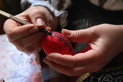 Painting the egg. Unidentified romanian woman painting the eggs for the traditional easter. Photo taken on: April 30th, 2014 in Bucovina, Romania royalty free stock photography