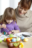 Painting eggs. Mother and daugther painting easter eggs together Stock Image