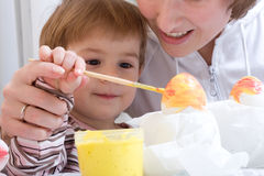Painting eggs before easter. Little child with mum painting eggs before easter Stock Images