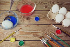 Painting eggs for Easter holiday celebration. On wooden table Stock Images