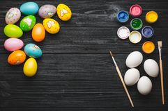 Painting eggs for Easter holiday on wooden table Royalty Free Stock Photo