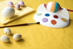 Painting eggs for Easter, with tool andbrush stock images