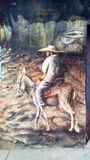 Painting of a elder man on a donkey by Julio Cesar Navarro Torres. Beautiful painting in Tlapehuala, Guerrero, Mexico representing a daily basis in the region of Stock Photo