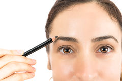 Painting the eyebrows with an eyebrow pencil Stock Photography
