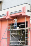 Painting the facade. In jeans and a work shirt facade paint roller standing on the scaffolding Stock Photo