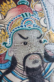 Painting face of ancient Asian warrior on a door in Wat Pho is t Stock Images