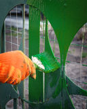 Painting the fence in the garden. Bright green paint Stock Photos