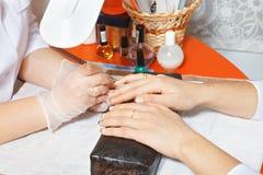Painting fingernails. Manicurist painting fingernails. Closeup hands horizontal shot Stock Images
