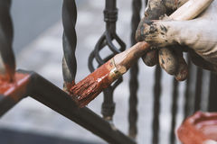 Painting forged railings on the stairs at the entrance of the house. Protection against rust. Working processes Stock Photos