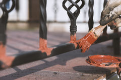 Painting forged railings on the stairs at the entrance of the house. Protection against rust. Stock Photos