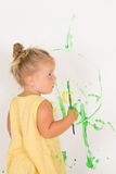 Painting is fun for kid. Happy child girl plays in the paint at home during the renovation Stock Image