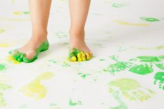 Painting is fun for kids. Dirty legs stands on paper with color prints Stock Photo