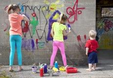 Painting fun. Kids having fun painting a concrete wall Stock Photo