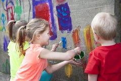 Painting fun. Three kids having fun painting a concrete wall Royalty Free Stock Photos
