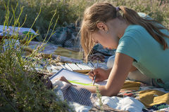 Painting girl. Girl paints at the nature Royalty Free Stock Photography