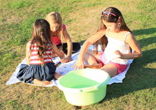 Painting kids. Girls painting their bare feet on green meadow Royalty Free Stock Images