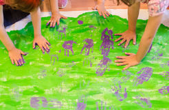 Painting green picture by purple children's palms stock image