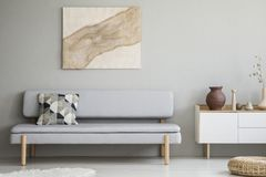 Painting on grey wall above settee with cushion in modern living. Room interior with cupboard. Real photo royalty free stock image