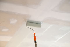 Painting a gypsum plaster ceiling with roller. Painting a gypsum plaster ceiling with painting roller stock images