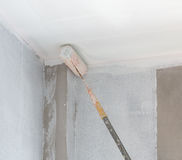 Painting a gypsum plaster ceiling with roller Stock Photo