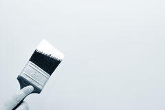 Painting. Hand with brush going to paint a wall Royalty Free Stock Photography