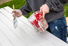 Paintbrush Painting by Hand. Painter paints white paint onto door using a brush and bucket of paint royalty free stock photos