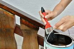 Painting a handrail. A wooden handrail is painted in brow color royalty free stock photography