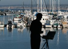Painting the Harbor. Artist painting the boats in a harbor Royalty Free Stock Images
