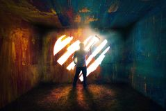 Painting a heart. A man paints a heart of light to escape royalty free stock photography