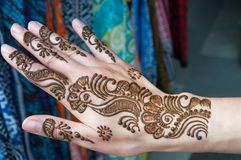 Painting Henna paste on woman's hand Stock Photo