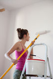 Painting her Apartment. Young woman uses paint roller to apply paint on her new room. House decoration Royalty Free Stock Photo