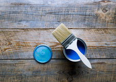 Painting at home with can blue paint on wooden background Royalty Free Stock Images
