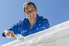 Painting House. A painter, painting a house on a blue sky background Stock Image