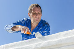Painting House. A painter, painting a house on a blue sky background Stock Images
