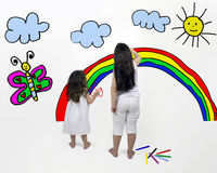 Painting illusions. Two girls paint a rainbow in the wall Stock Photo