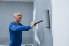 Painting An Interior. High angle view of a male builder using a roller to paint walls of an interior Royalty Free Stock Image