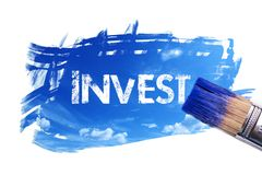 Painting invest word. Paintbrush is painting sky with invest word on white screen , isolated background Stock Images