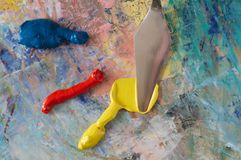 Painting knife spreading oil colour. On a wooden palette stock photos