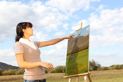 Painting landscape. Young woman painting landscape Royalty Free Stock Photo